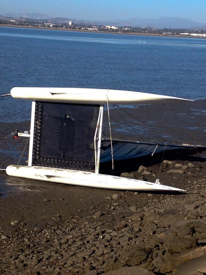 Catamaran flipped over on muddy bank of San Diego Bay